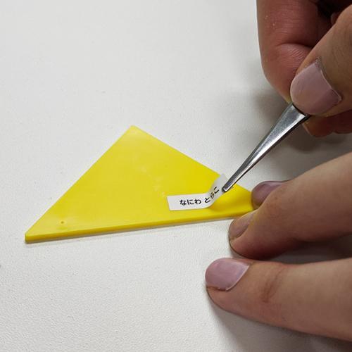 無地小サイズのお名前シールを色板カードに貼っている様子