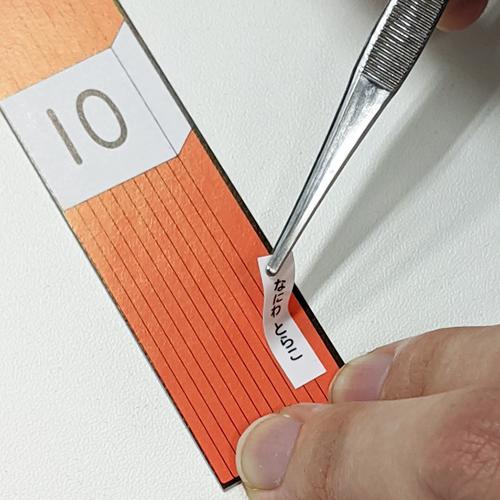 無地小サイズ(縦書き)のお名前シールを束カードに貼っている様子