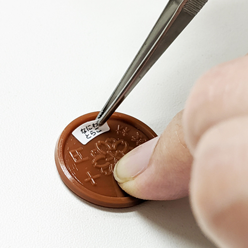 コインサイズのお名前シールを10円に貼っている様子