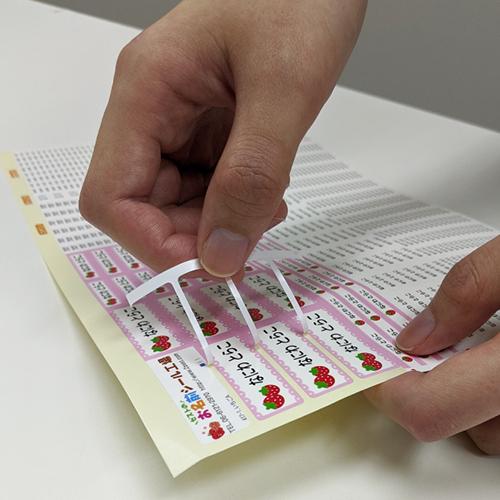 算数セット用お名前シールの余白の赤い矢印を剥がしている様子