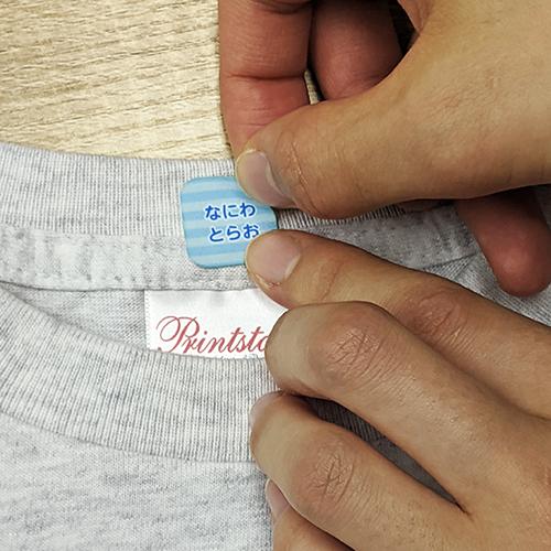 13.布用お名前シールをTシャツに貼る様子