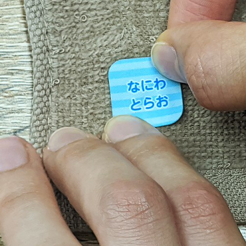 7.布用お名前シールをタオルに貼る様子