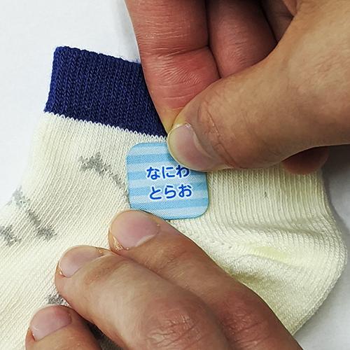 9.布用お名前シールを靴下に貼る様子
